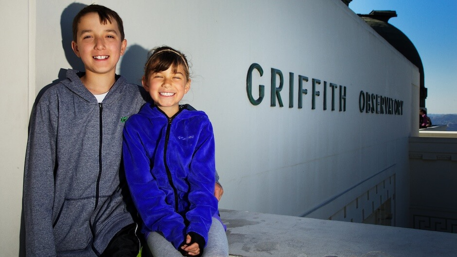 Nathan and Devyn posing in front of the Griffith Observatory sign. © Mike Wong